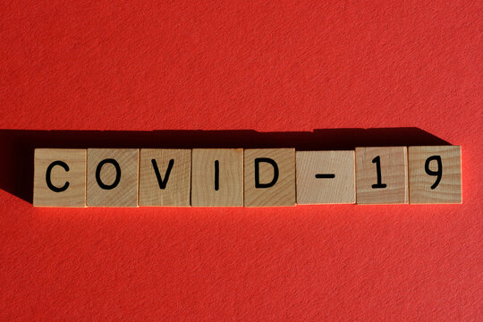Covid-19 word in wooden alphabet letters isolated on red background