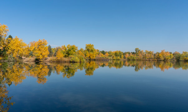 Colorful Fall Trees Wrapping Around Lake with Reflections in Water