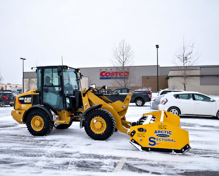 BRAINERD, MN - 19 DEC 2019: Snow removal machine for clearing Costco parking lot after winter storm. Yellow front end loader with snow plow blade.