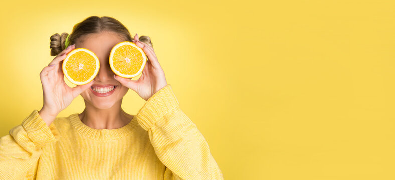 young blonde woman holding orange slice over her face, smiling on yellow background, wearing yellow sweater, with copy space