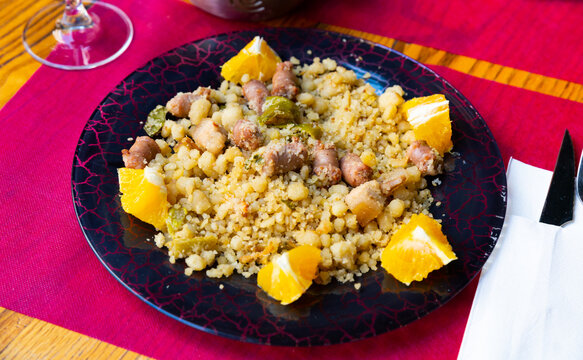 Typical spanish dish from semolina flour with longaliza sausage, served with orange