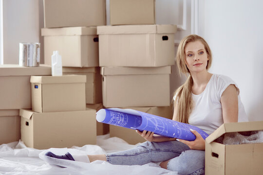 Girl sitting among boxes makes marks on the plan of the apartment
