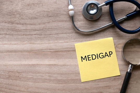Top view of stethoscope, magnifying glass and yellow paper note written with Medigap on wooden background with copy space.