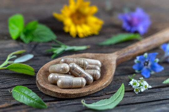 Holistic medicine approach. Healthy food eating, dietary supplements, healing herbs and flowers. wooden background, c.