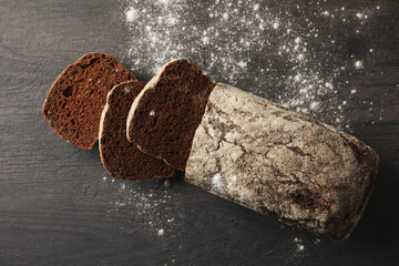 Fresh baked rye bread and flour on black background