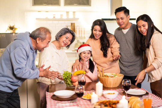 Asian big family sing a song while preparing foods for Christmas party