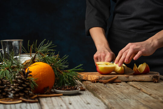 Chef cuts with knife apple on wooden chopped board for preparing aromatic muled wine with fragrant species on christmas composition background. Backstage of making hot winter drink. Traditional recipe