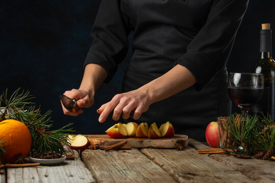 Chef cuts with knife apple on wooden chopped board for preparing aromatic muled wine with fragrant species on wooden table background. Backstage of making hot winter drink. Traditional recipe.