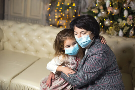 Grandmother and granddaughter on the sofa in the living room with Christmas decor hugging in medical masks on their faces. A family holiday during the outbreak of coronavirus and disease. New Year