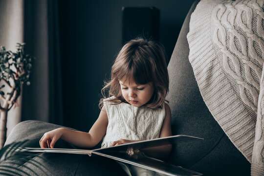 Little baby girl reading a book at home