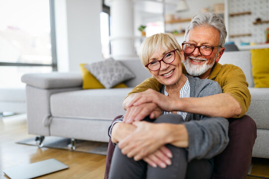 Happy romantic senior couple hugging and enjoying retirement at home