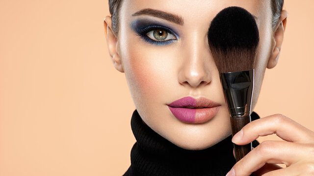 Portrait of a girl with cosmetic brush at face. Woman covering one eye on the face using makeup brush. One half face of a beautiful white woman with  bright makeup and the other is natural.