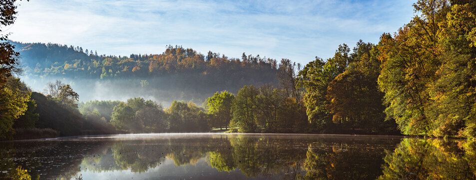 Lake fog landscape with Autumn foliage and tree reflections in Styria, Thal, Austria