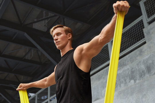 Young Man Stretching With Resistance Band Against Concrete Wall Outdoors. Handsome Caucasian Sportsman With Strong Muscular Body In Fashion Sportswear Doing Stretch Workout.