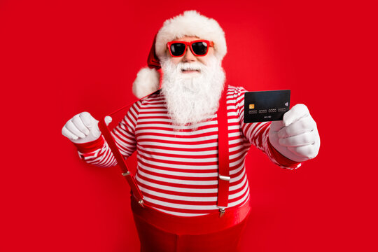 Portrait of his he nice handsome cheerful confident bearded fat Santa give you offer bank card payment service spend money budget having fun isolated bright vivid shine vibrant red color background
