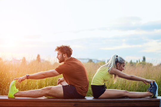 Young adult sporty couple working out outdoors in urban surroundings.