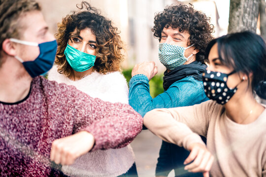 Multiracial friends greeting with elbow bump wearing face protection - New normal lifestyle concept with young people covered by disposable mask - Selective focus on middle left woman