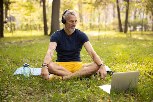 Smiling athletic male practicing yoga online in nature