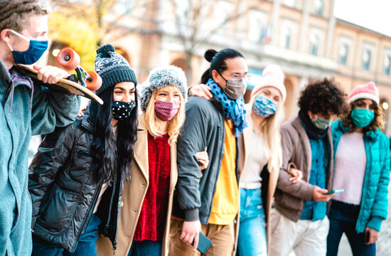 Millennial people group walking and having fun together wearing face mask at city center - New normal friendship concept with multicultural friends on winter fashion clothes - Bright vivid filter