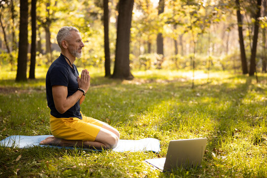 Calm mature male doing meditation with laptop outdoors
