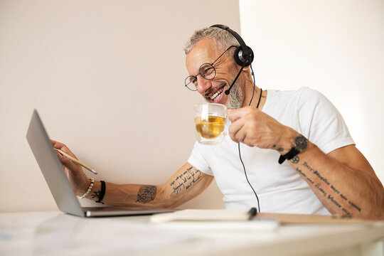 Worker with tattooed arms drinking tea and touching the screen