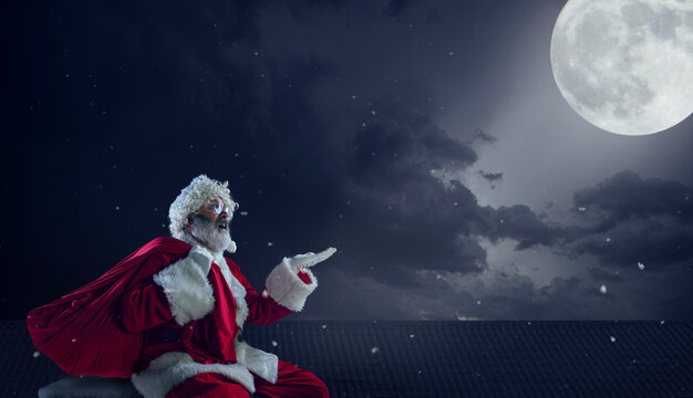 Emotional Santa Claus congratulating with New Year 2021 and Christmas. Man in traditional costume sitting on house roof with full moon on background in midnight. Winter, holidays, sales. Copyspace.