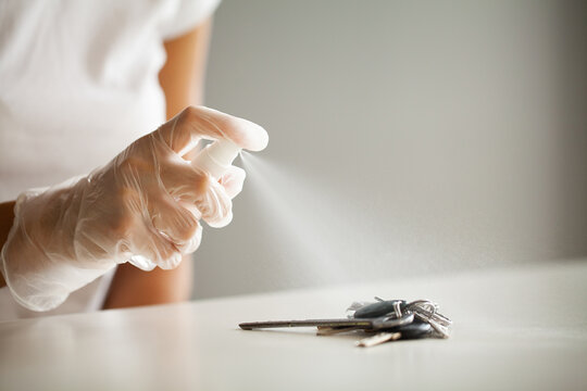 Woman disinfecting keys with disinfectant on the table