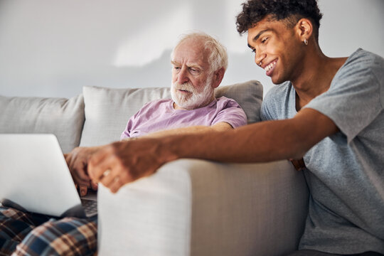 Aged man and his caregiver surfing the Internet