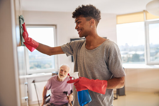 Smiling volunteer cleaning the room of a senior man