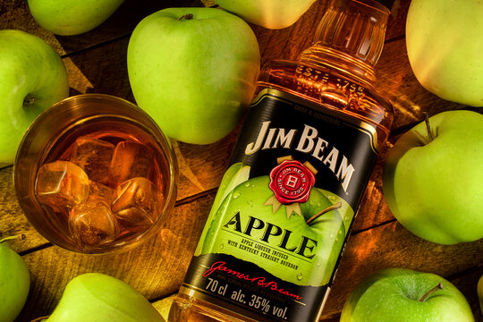 Still life with a bottle of Jim Beam Apple Bourbon , liqueur from Kentucky , with a glass of cold whiskey on ice on a wooden brown background of boards, surrounded by juicy green apples