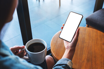 Mockup image of a woman holding mobile phone with blank white desktop screen while drinking coffee