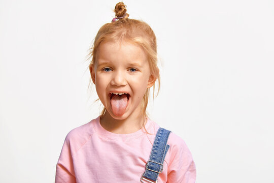 Smiling 4-5 year old little girl shows tongue. Caucasian cute kid in pink sweatshirt, on white background