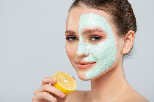 Portrait of a beautiful woman with a blue cream mask on her face and a slice of lemon. Close-up