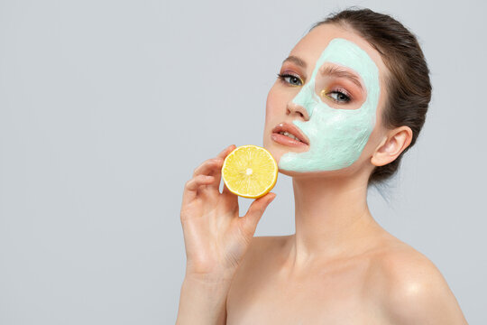 brunette woman is holding a slice of lemon in front of her face. Photo of a woman with a moisturizing face mask. Beauty and skin care concept