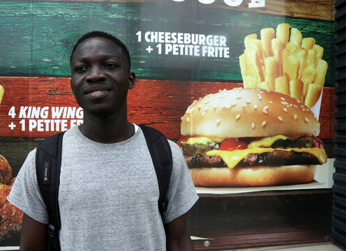 Student Ange Kouame, 23, reacts to the 2020 U.S. presidential election in front of a fast food restaurant during a vox pop in Abidjan
