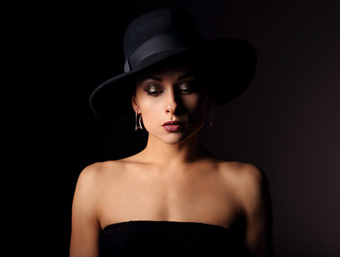 Beautiful makeup woman with elegant healthy neck, nude back and shoulder on black background in fashion hat with empty copy space. Closeup front view portrait.