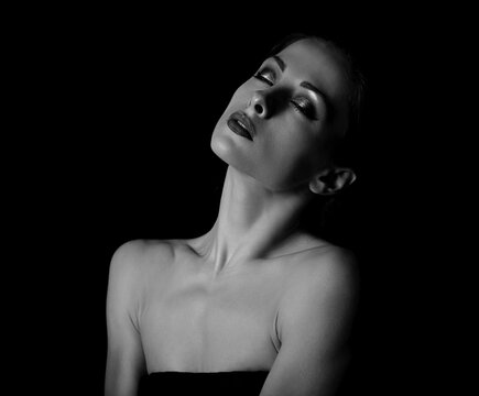 Beautiful elegant makeup woman with healthy neck and skin, nude shoulders on dark black background with empty copy space. Closeup portrait. Art.