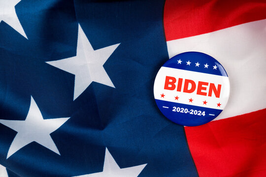 Biden 2020-2024 text on american election vote button on united states national flag. 2020 presidential election concept.
