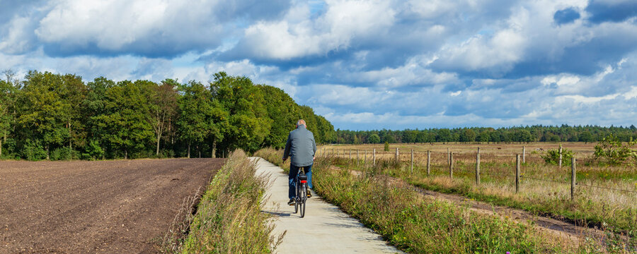 Man cycling between farm land with forest in the background in Gelderland in the Netherlands