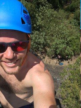 Happy man climbing with a blue helmet