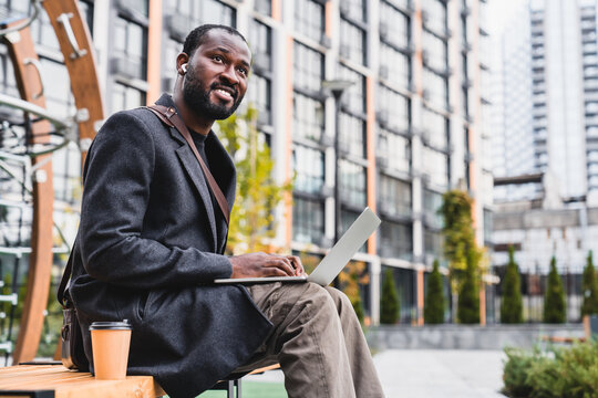 Smiling confident 30s african man using laptop with cup of coffee in city area