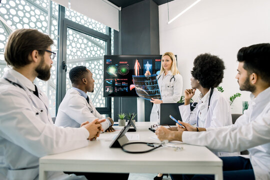 Medicine, continuing education concept. Caucasian blond woman, experienced and competent doctor, showing a presentation and speaking about new diagnostics and treatment in a seminar for colleagues