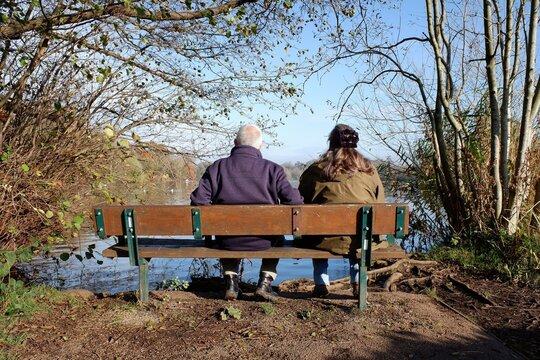 Couple sitting on bench looking at Bury Lake in Rickmansworth, Hertfordshire, England, UK