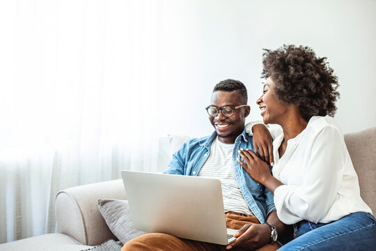 Young black couple using laptop sitting on the sofa at home. Full length of couple watching movie on laptop. Happy man and woman are relaxing on couch. They are spending leisure time at home.