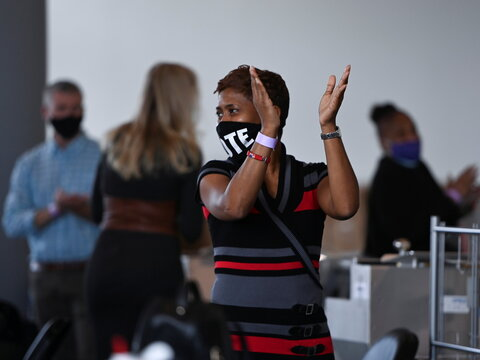 A woman claps hands after a news conference held by Chairman of Fulton County Board of Commissioners Robb Pitts and Fulton County Registration and Elections Director Richard Barron in Atlanta