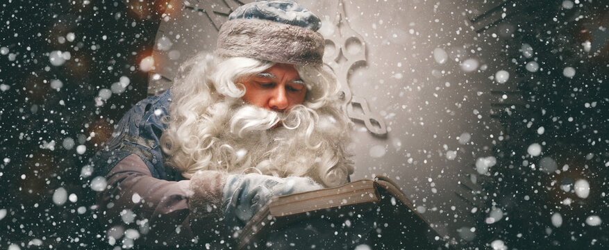 Magical russian Santa Claus (Grandfather Frost) in a blue caftan sits in front of the christmas tree and read large opened wishes book. Panoramic banner. Christmas concept