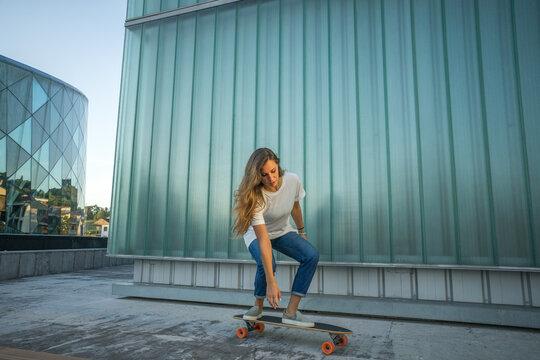 mujer con camiseta blanca y vaqueros patinando en skate en un entorno urbano