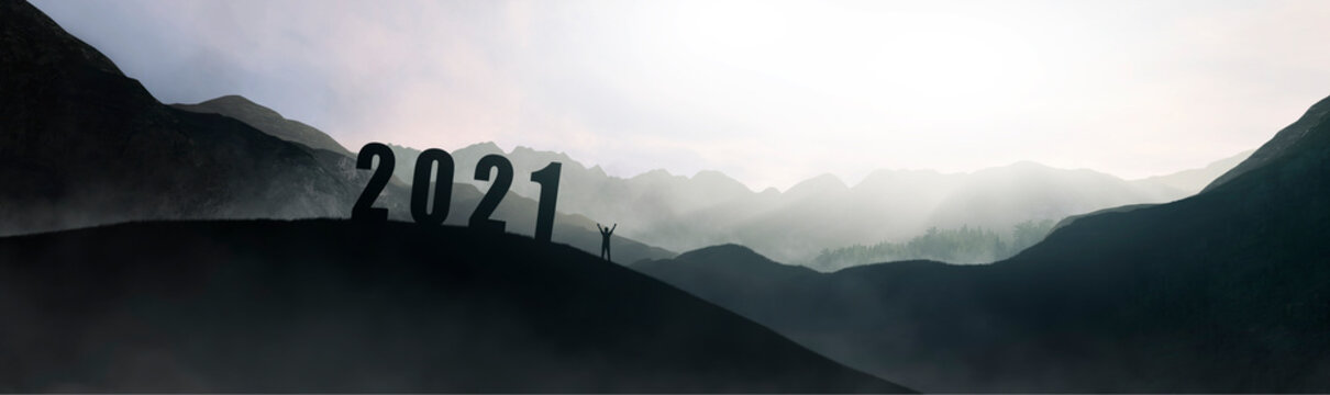silhouette of number 2021 on mountain next to man celebrating, new year concept