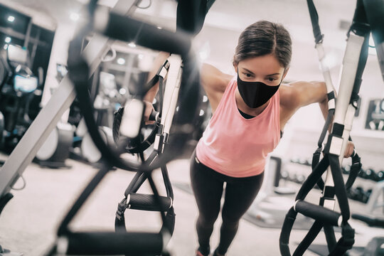 Woman training at gym wearing face mask for Coronavirus prevention while exercising strength indoors.
