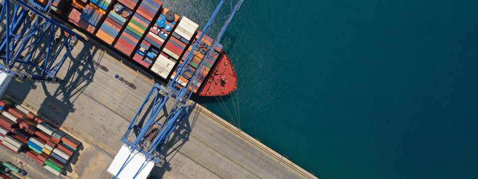 Aerial top down ultra wide photo of industrial cargo container ship loading in logistics terminal port